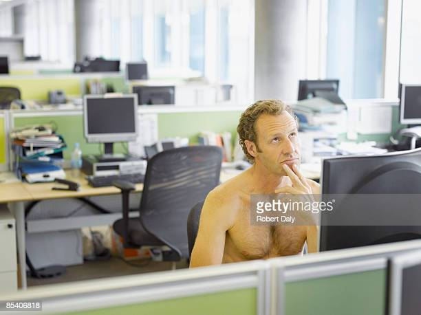 Nude businessman sitting at desk