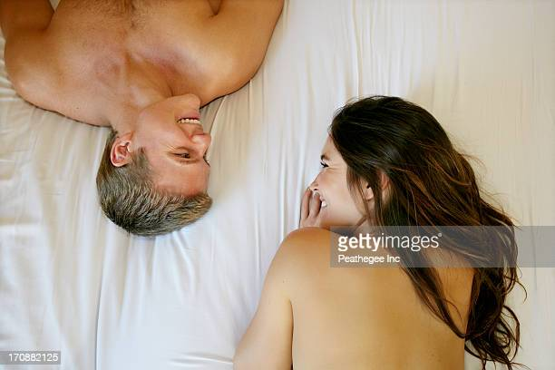 Nude Caucasian couple relaxing on bed