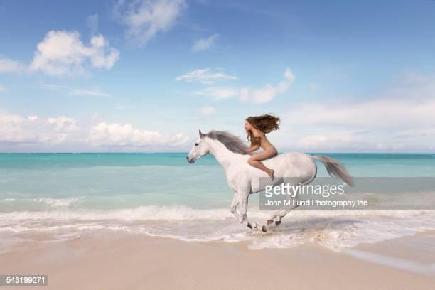 Nude Caucasian woman riding horse on beach