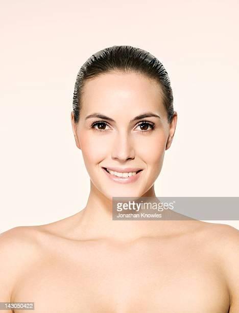 Nude dark hair female smiling, head and shoulders