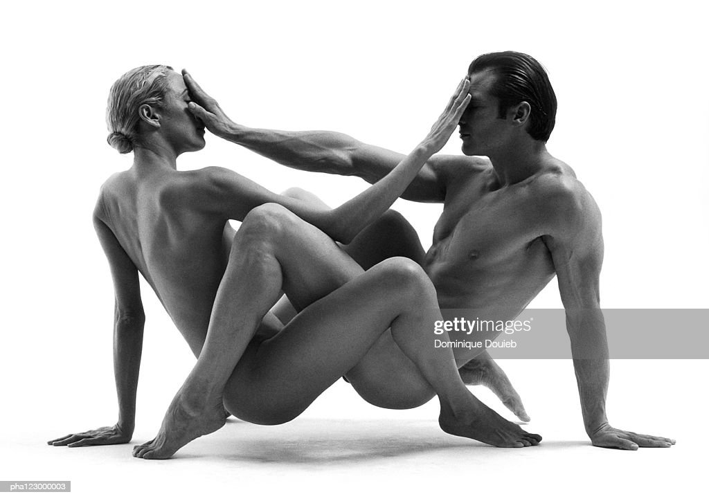 Nude man and nude woman intertwined, facing each other with hands covering faces, B&W : Stock Photo