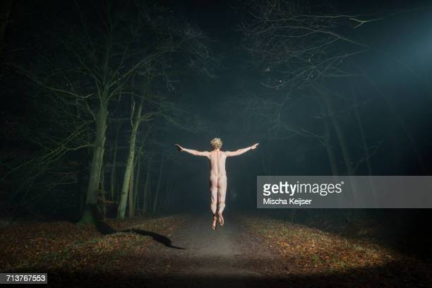Nude man jumping in woods at night, rear view, Breda, Noord-Brabant, Netherlands
