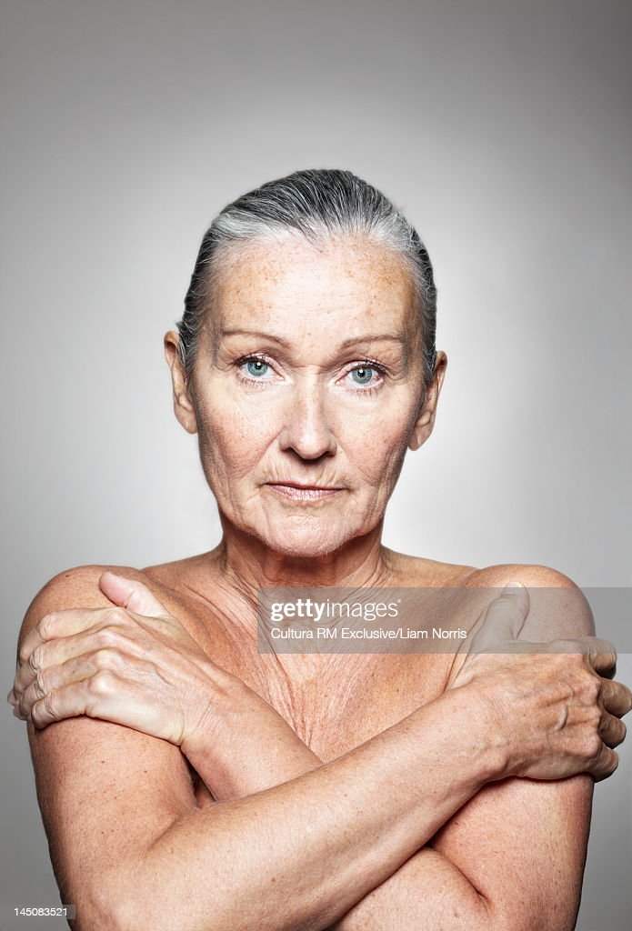Nude older woman holding her shoulders
