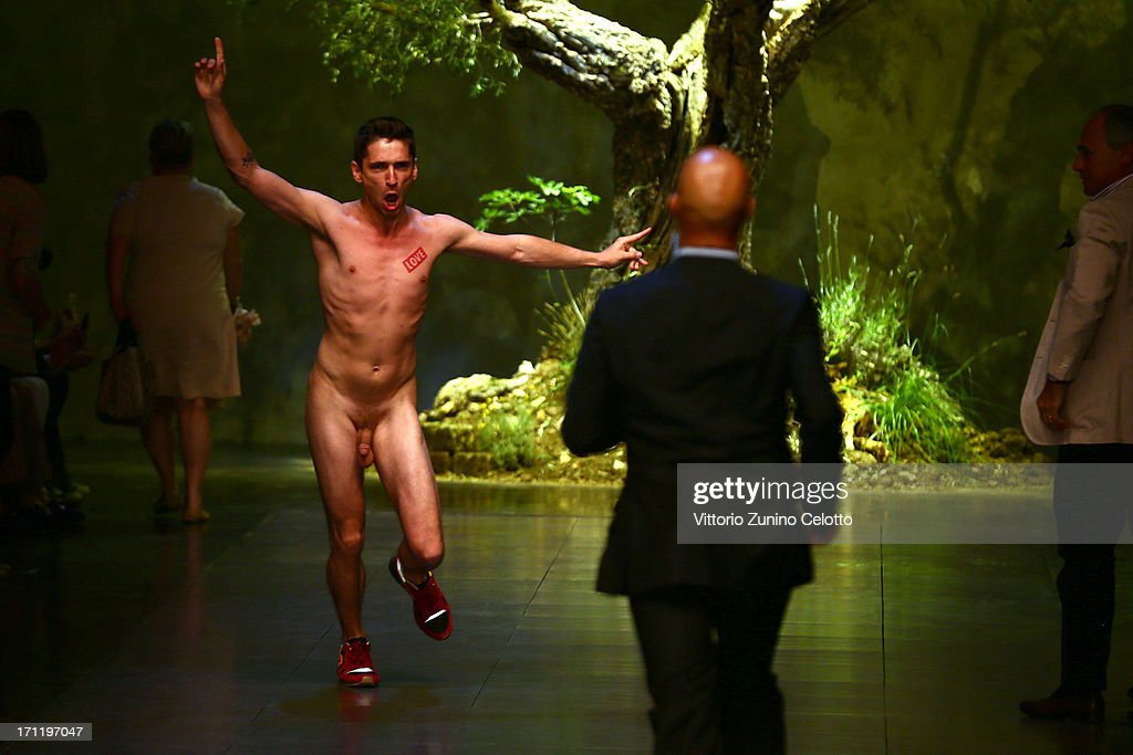 A nude protester runs onto the runway at the Dolce & Gabbana show during Milan Menswear Fashion Week Spring Summer 2014 on June 22, 2013 in Milan, Italy.
