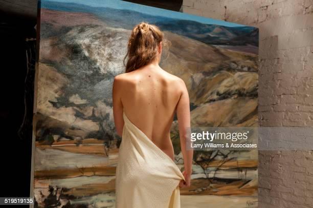 Nude woman admiring painting in art gallery