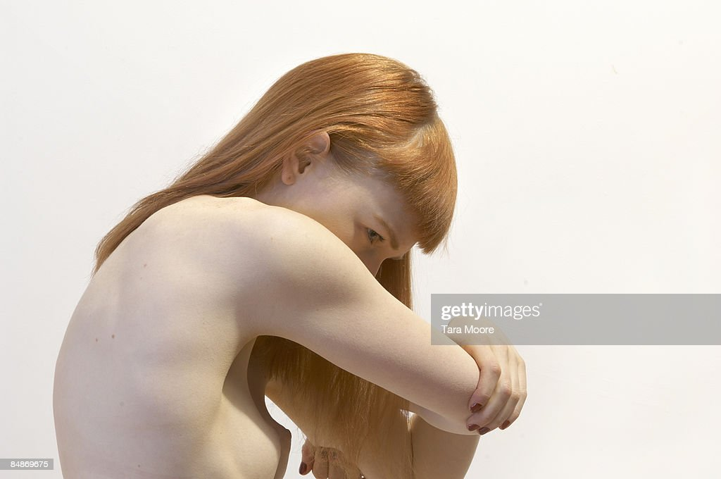 nude woman covering face with arms : Stock Photo