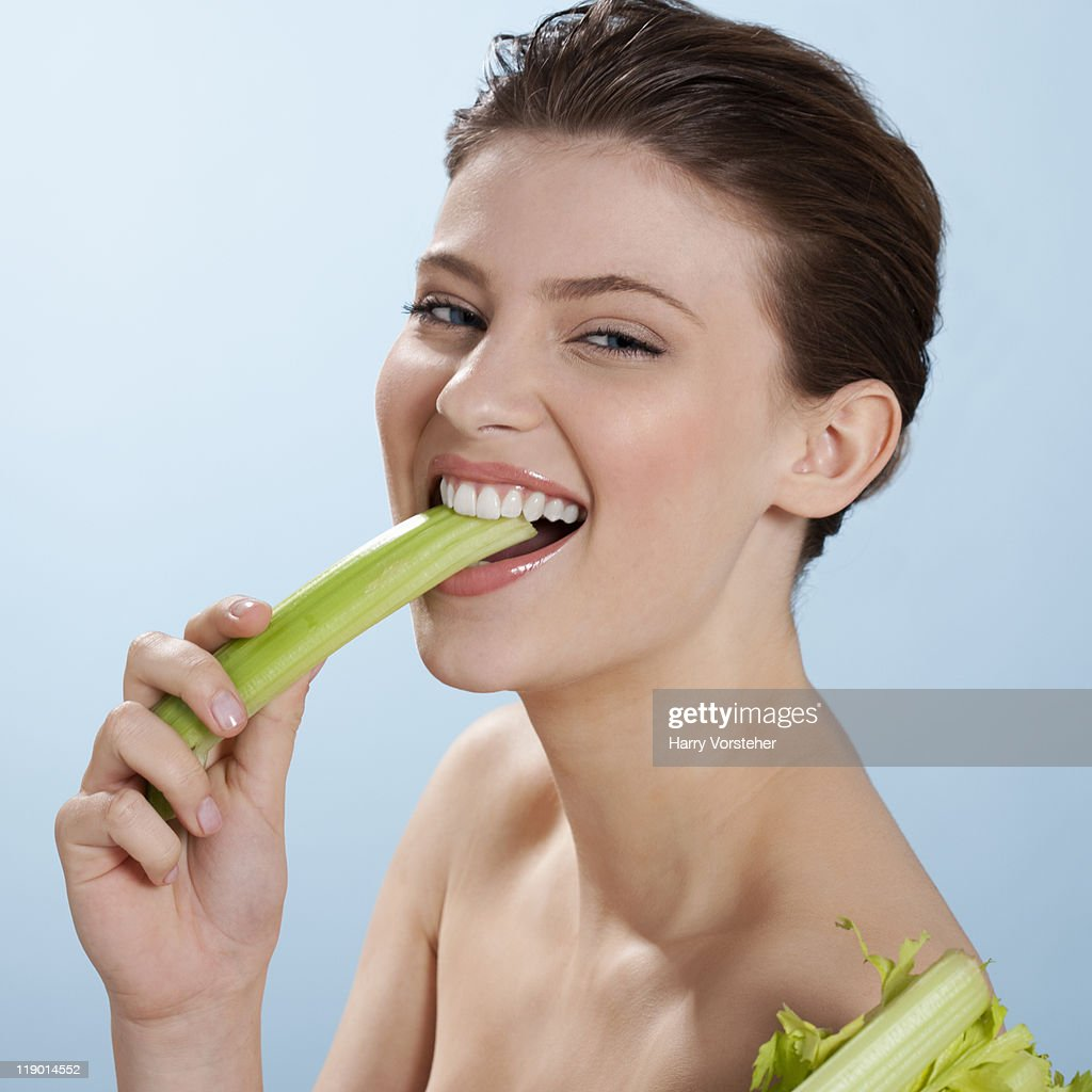 Nude woman eating celery : Stock Photo