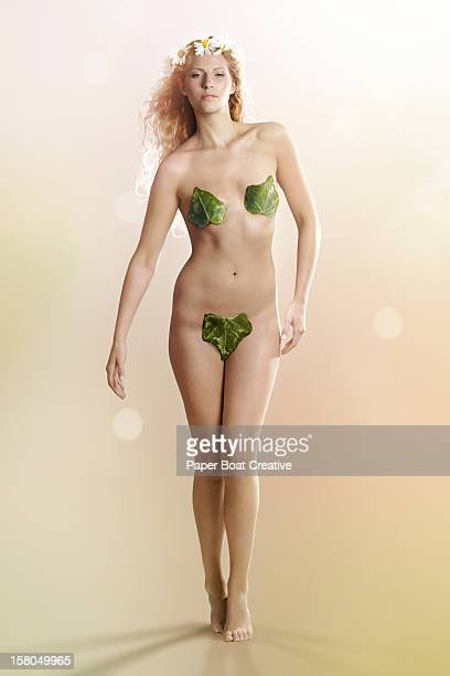 Nude woman like Eve with leaves covering her body