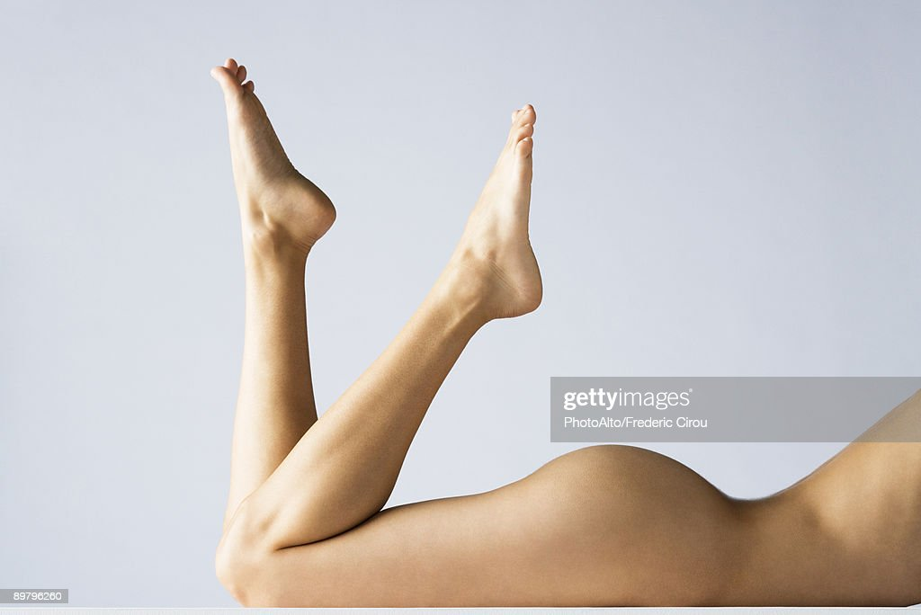 Nude woman lying on stomach with legs up, cropped : Stock Photo