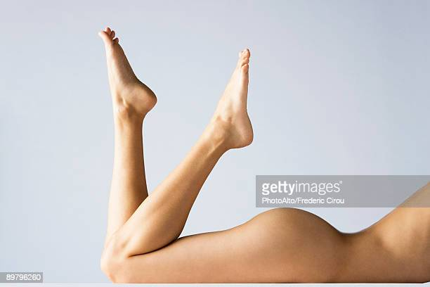 Nude woman lying on stomach with legs up, cropped