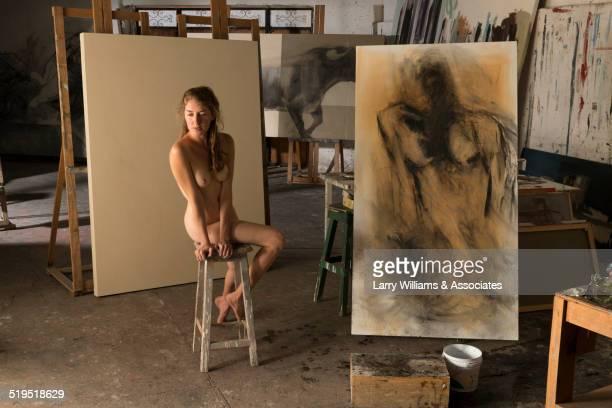 Nude woman modeling for artist in studio