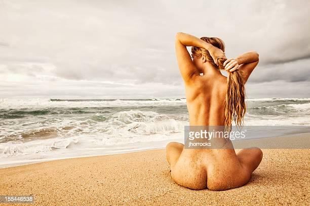 Nackte Frau am Strand mit Sand bedeckt