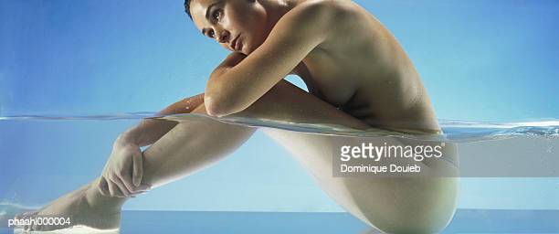 Nude woman sitting in water, side view