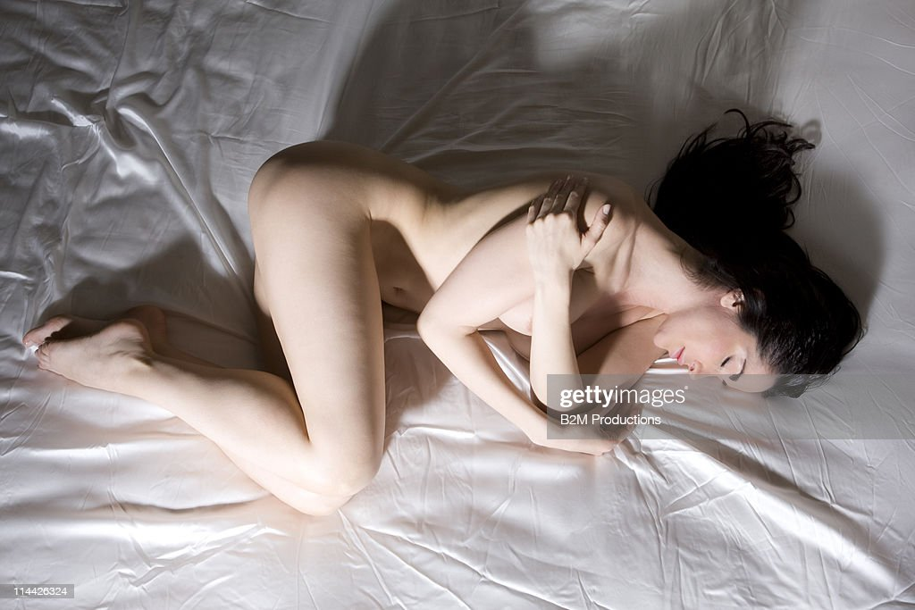 Nude woman sleeping on bed : Stock Photo