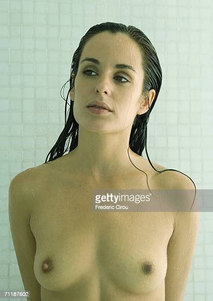Nude woman standing in shower