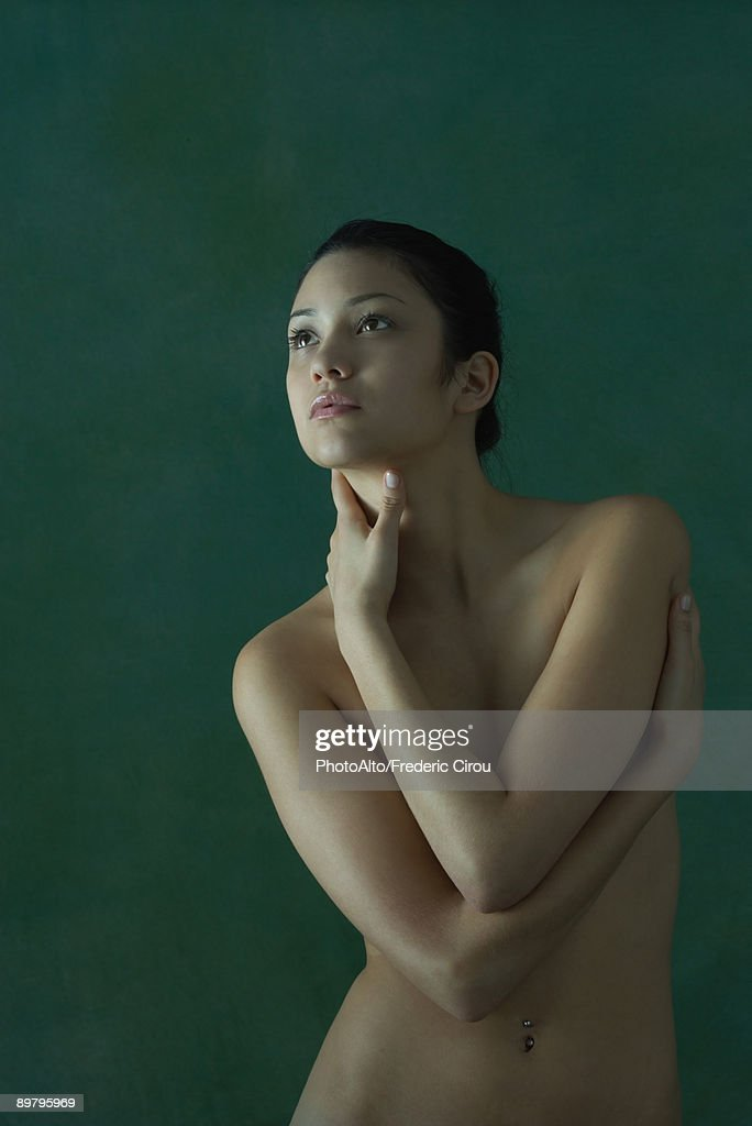 Nude woman standing with arms folded over chest, looking up : Stock Photo