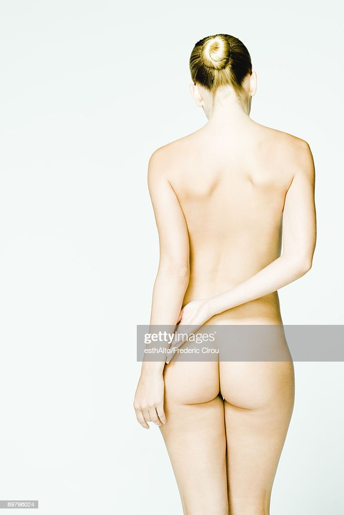 Nude woman standing with hands behind back, rear view : Stock Photo