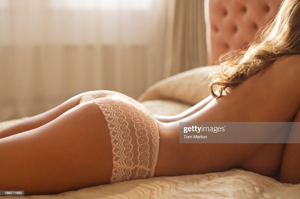 Nude woman wearing panties in bed : Stock Photo