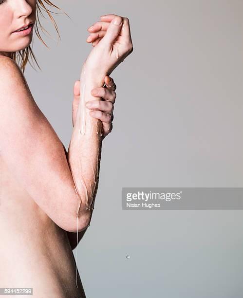 Nude woman with oil dripping off arm