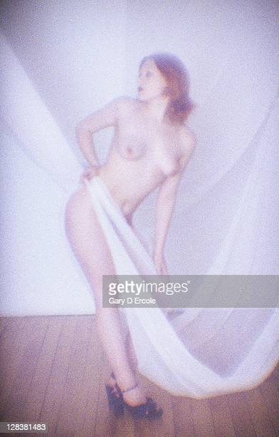 Nude woman with red hair and transparent curtain