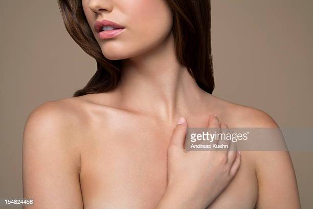 Nude young woman with hand across chest, cropped.