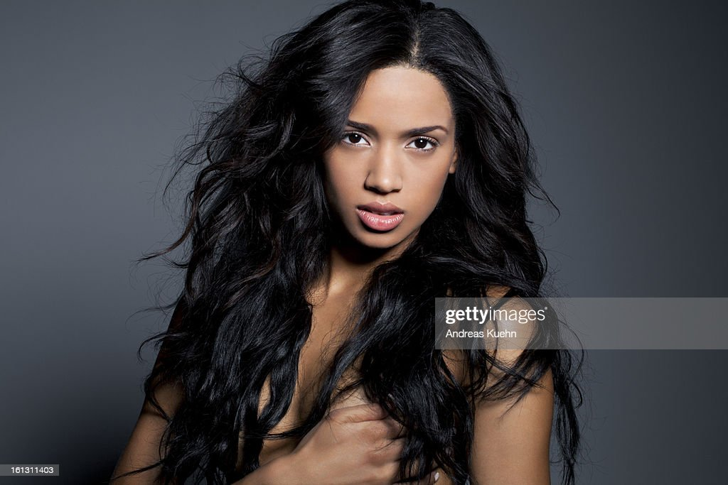 Nude young woman with long, black hair, portrait.