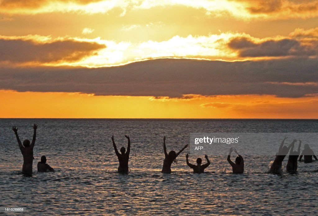 Nudists take part in the annual North East Skinny Dip as the sun rises at Druridge Bay in Northumberland, northeast England on September 22, 2013. Around 200 bathers once again braved the cold in an attempt to break the world record for the largest skinny-dip.