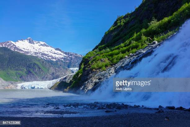 Nugget Falls cascades into Mendenhall Lake with Mendenhall Glacier distant.