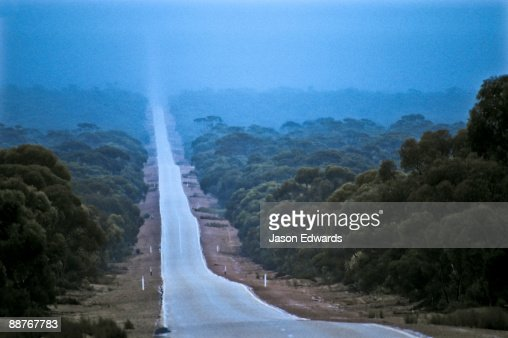 A rain storm falls over a long, straight road on the Nullarbor Plain.