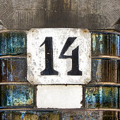 Weathered house number fourteen. Black lettering on a white background.
