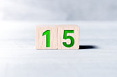 Number 15 Formed By Wooden Blocks On White Table