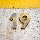 brass house number nineteen on a marble wall