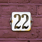 enameled house number twenty two. Black lettering on a white background