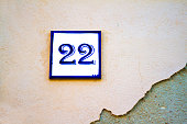 A vintage white and blue ceramic number 22 address tile on an old pale pink wall. Shot in Italy. Copy space available.