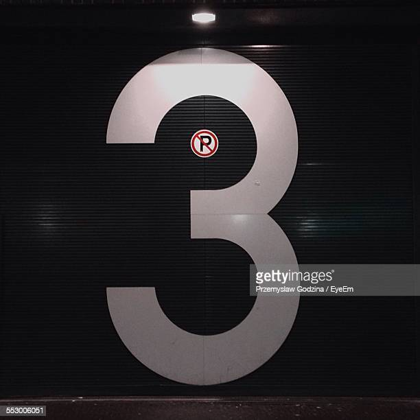 Number 3 And No Parking Sign On Closed Shutter During Night