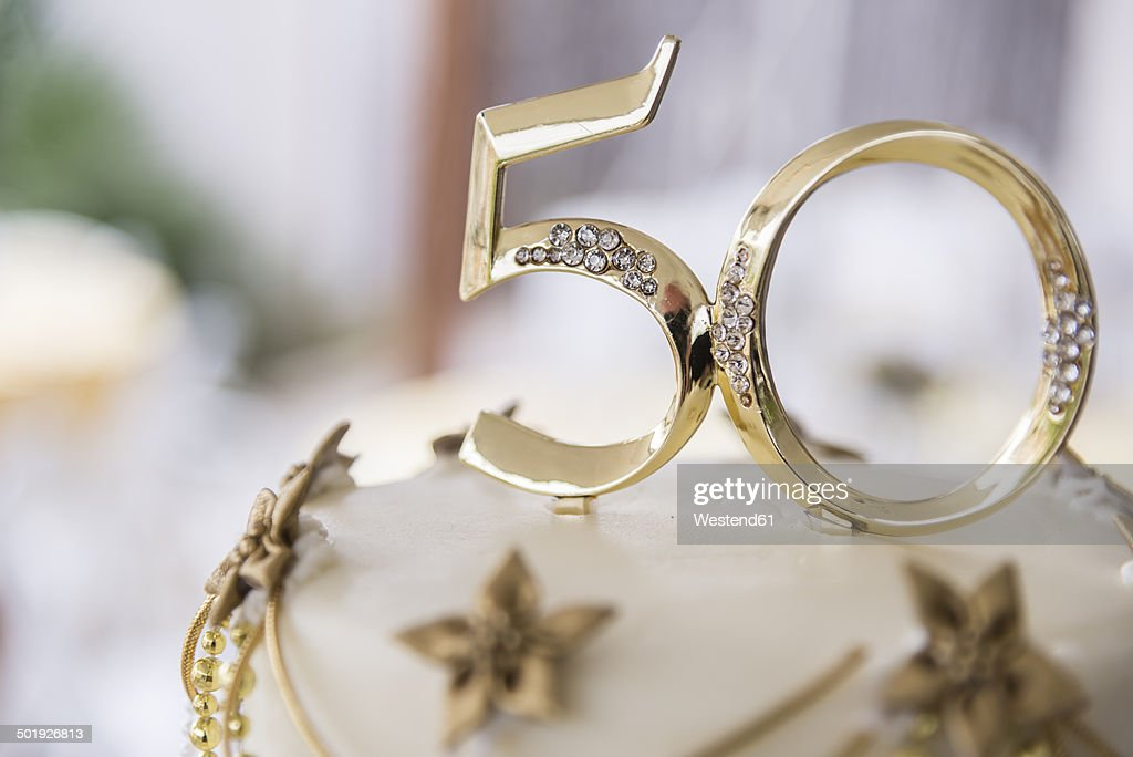 Number 50 in golden plastic attached to the top of a wedding anniversary cake