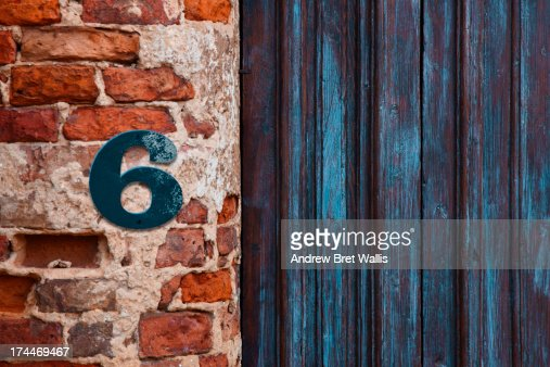 Number 6 sign aginst brickwork close to a doorway : Stock Photo