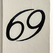 house number sixty nine, hand pained on a door post