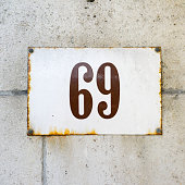 enameled house number on a wall of natural stone