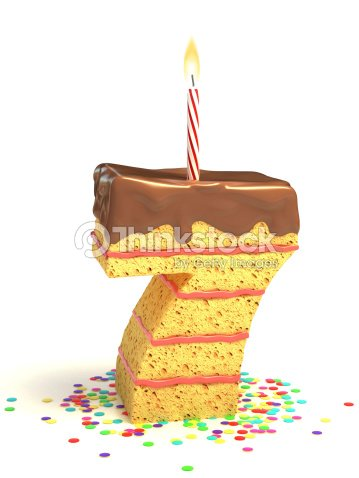 Number 7 Shaped Chocolate Birthday Cake With Lit Candle Stock Photo