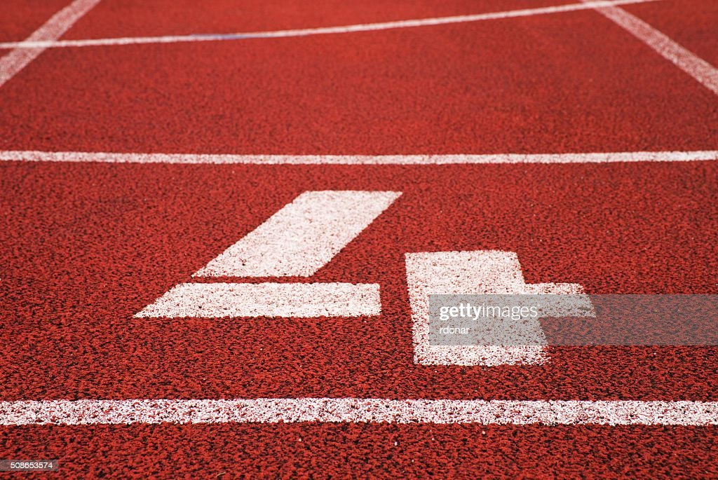 Number four. White track number on red rubber racetrack : Stock Photo