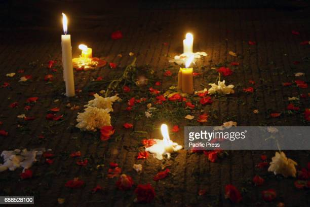 A number of people lit candles and sprinkled flowers at the site of a suicide bomb attack at Kampung Melayu bus station Jakarta on Thursday night May...