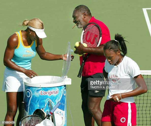 Number one seed Serena Williams and her sister number two seed Venus Williams take a break from a morning practice sesssion with their father Richard...