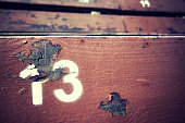 Number thirteen painted on an old wooden seat, conceptual picture with copy space on the right.