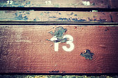 Number thirteen painted on an old wooden seat, conceptual picture.