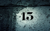 Number thirteen in stone wall, sign and symbol