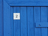 house number plate with number 2 on a blue painted rustic wooden door