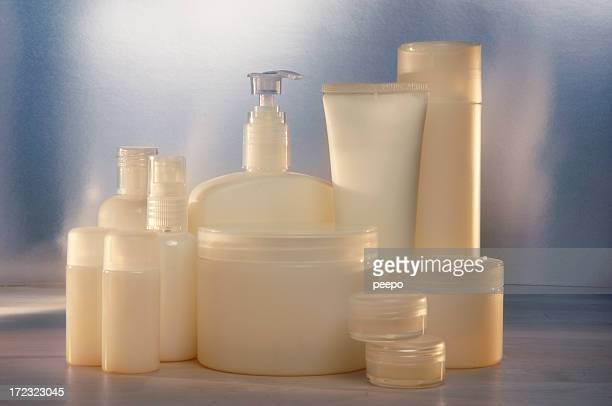 Numerous blank beige cosmetic containers in various sizes.