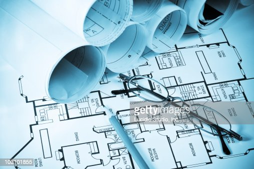 Numerous blueprints, reading glasses and a pencil : Stock Photo