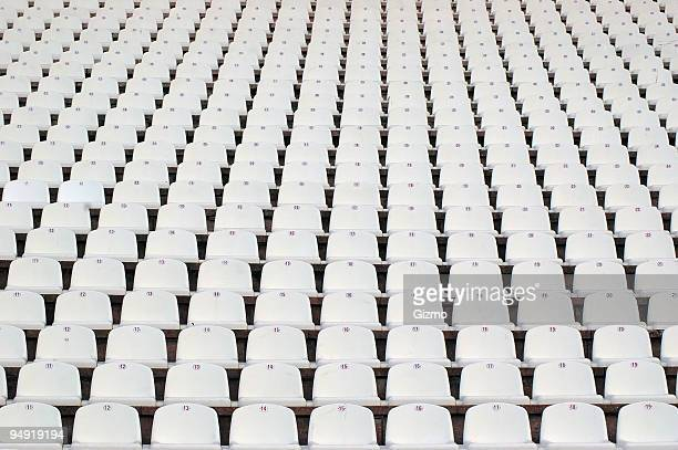 Numerous rows of white stadium seats